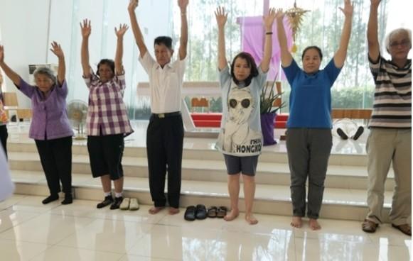 Patienten strecken ihre Arme hoch um zu zeigen, dass ihre 'eingefrorenen' Schultern und Arme wieder geheilt sind.