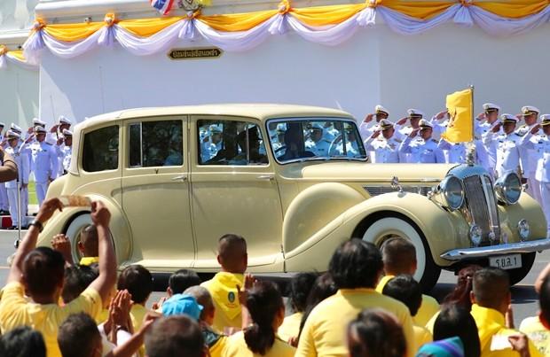 Ihre Majestäten, König Maha Vajiralongkorn und Königin Suthida fahren am Samstag durch Bangkok und werden von ZXuschauern bejubelt. (AP Photo/Sakchai Lalit)