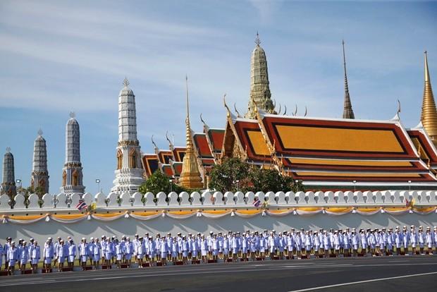Offizielle und Beamte stehen außerhalb des Grand Palace in Bangkok während der Krönungszeremonie. (AP Foto/Sakchai Lalit)