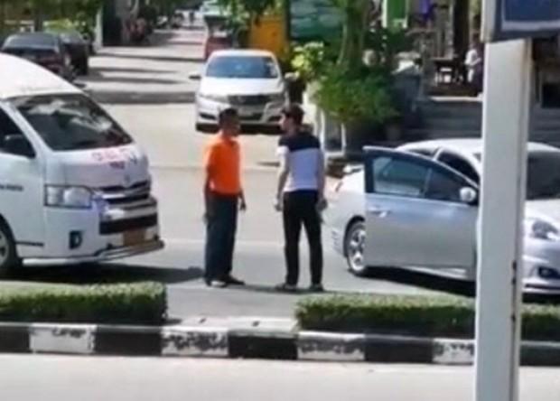 Eindeutig ist zu erkennen, wie der Aunbekannte Autofahrer den Minibusfahrer mit einer Pistole bedroht.