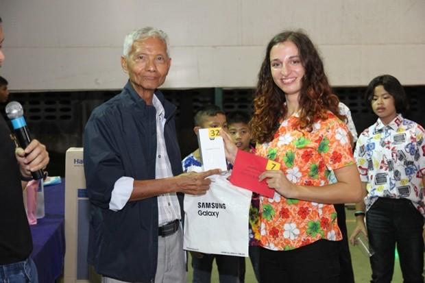 Samphan Akarapongpanitch, überreicht den ausländischen Volontären Handy's und Geldgeschenke.