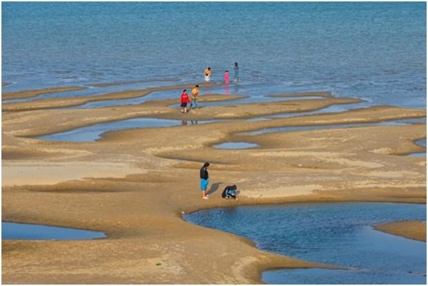 Touristen spielen auf Sandbänken mitten im Fluss. Ein Phänomen, das es bisher nicht gab. (AP Photo/Chessadaporn Buasai)