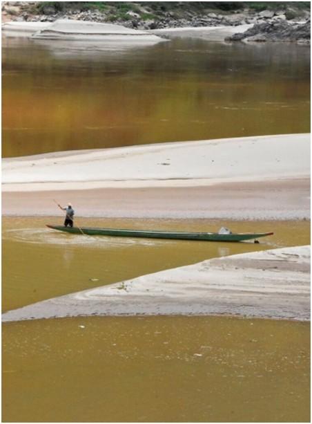 Ein Mann rudert ein traditionelles Mekong River Boot in seichtem Wasser im Wieng Kaen Distrikt bei Chiang Rai. (Photo: International Rivers via AP)