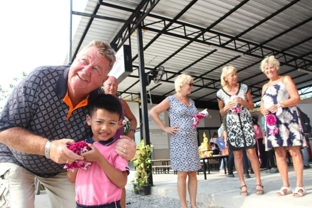 Kinder überreichen Renee van Goosen und anderen holländischen Freunden Blumen.