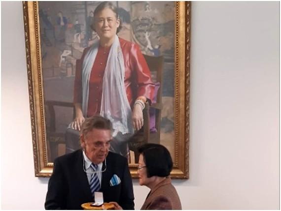 Axel Brauer erhält die Ehrennadel von Assoc. Prof. Khunying Sumonta Promboon, unter dem Bildnis Ihrer Königlichen Hoheit, Prinzessin Maha Chakri Sirindhorn.