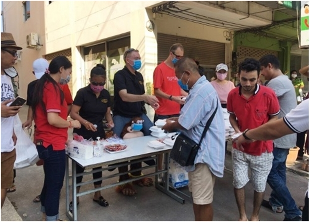Supattra Chonlapol und Brad Rogers,die Eigentümer der Skyfall a-Go-Go und JP Republic, geben mit Freunden das Essen an die Bedürftigen im Flybird Markt am 30. Märzaus.