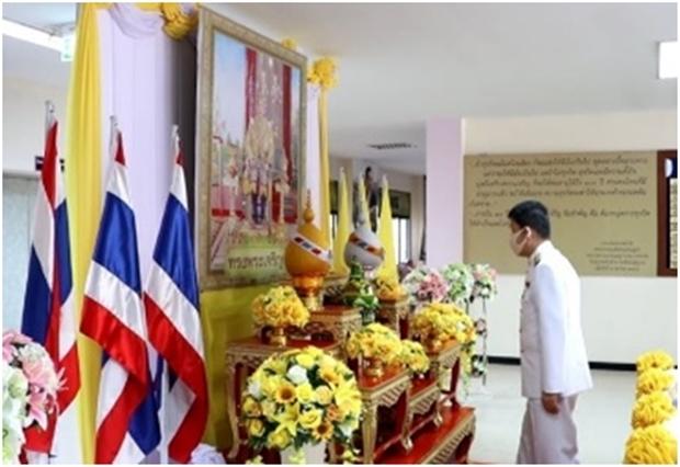 Offizielle Beamte erweisen dem Bildnis des Königs die Ehre.