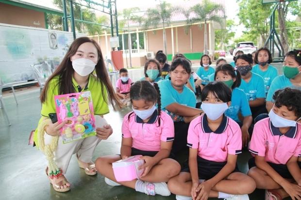 Hübsche Mädchen vom Chinesischen Touristenhilfscenter shcneken den Kinder Spielzeug.
