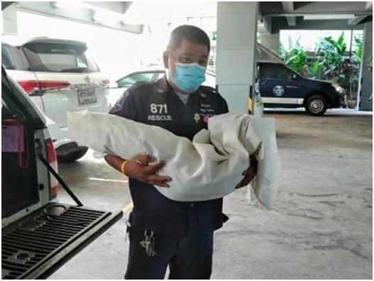 Ein Rettungsarbeiter trägt die kleine Leiche weg.
