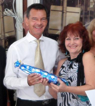 Der Österreichische Generalkonsul Rudolf Hofer, der an diesem Tag seinen Geburtstag feierte, erhält von von Chefredakteurin Elfi Seitz ein Geburtstagsgeschenk.