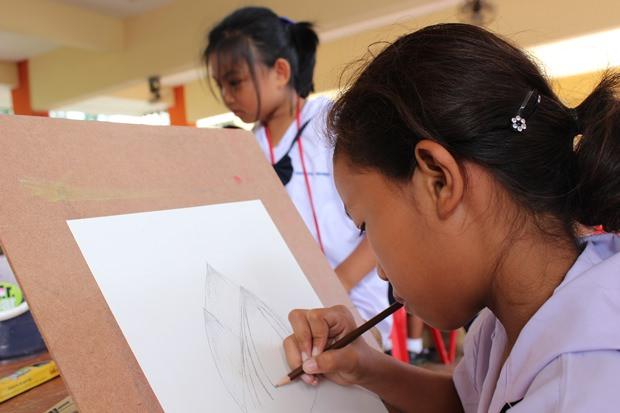 Schüler versuchen sich in der Thai-Malerei.
