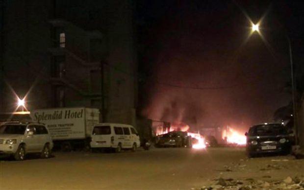 Die Lobby des Hotels steht in hellen Flammen, während Sicherheitsbeamte die geretteten Geiseln in Sicherheit bringen. (AP Television)