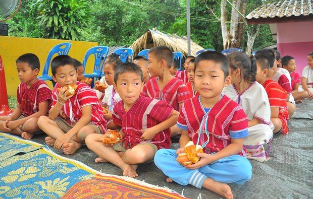 Die Kinder wissen nicht genau was sie mit den dicken Wurstsemmeln anfangen sollen - aber nach dem ersten Versuch schmeckt es ihnen.