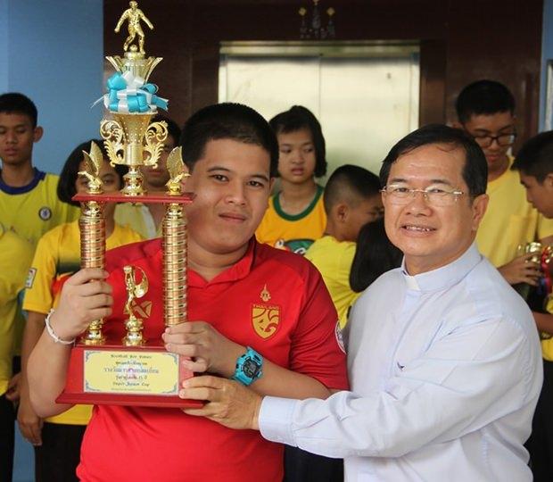 Das siegreiche rote Team erhält den Pokal aus den Händen von Father Michael.
