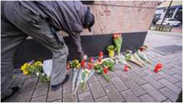 Menschen legen am Tatort Blumen nieder.