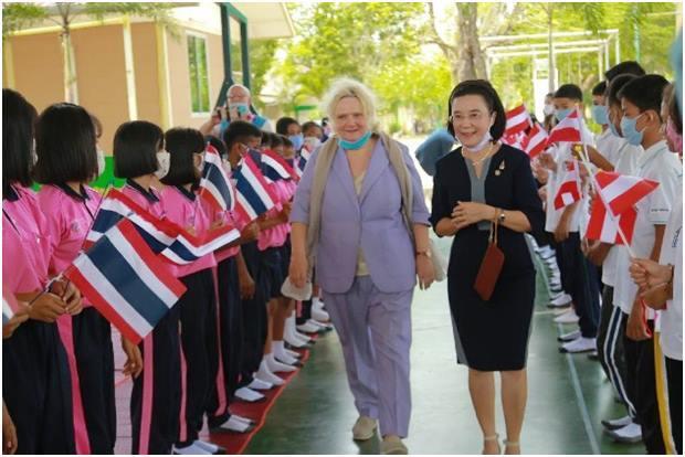 Die Botschafterin schreitet mit Radchada Chomjinda durch ein Spalier der Kinder die Thai- und Österreichische Flaggen halten.