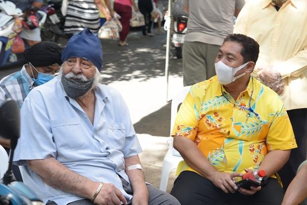 Amrik Singh sitzt gemeinsam mit Bürgermeister Sonthaya Khunplome während Essen an Arbeitslose am 8. Juni 2020 verteilt wird. Die war die letzte Wohltätigkeit an der Amrik beteiligt war.