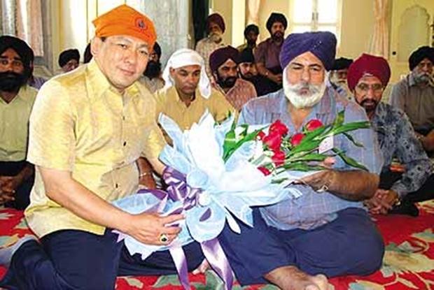 Amriks alter Freund, Chanyuth Hengtrakul, überreicht ihm ein Blumenbouquet zu einer Feier.